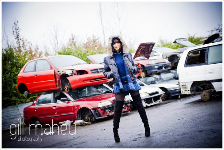 portrait of beautiful young woman in car breakers yard in geneva by by portrait and wedding photographer Gill Maheu