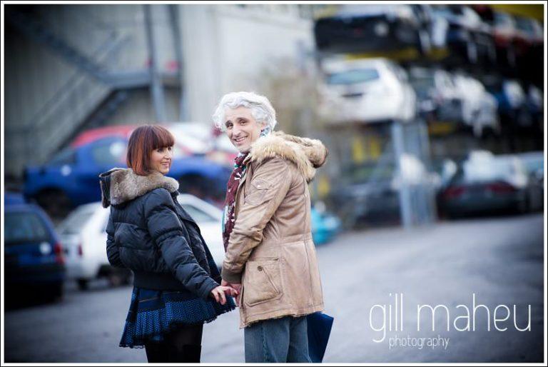 couple lookig back at camera as they walk away at  at ultra stylish engagement shoot at Geneva Car Breakers yard by Gill Maheu Photography , photographe de mariage