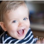 very cheeky grinned toddler laughing for the photographer  by lifestyle photographer Gill Maheu
