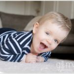 toddler with gorgeous cheeky grin crawling across the floor towards the camera  by lifestyle photographer Gill Maheu