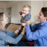 young toddler with gorgeous smile being cuddles by parents by lifestyle photographer Gill Maheu Photography