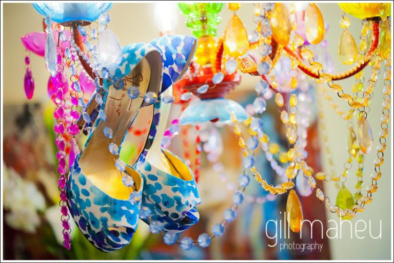 Gorgeous Kurt Steiger high heels hanging from brightly coloured chandelier - wedding detail by Gill Maheu Photography photographe de mariage