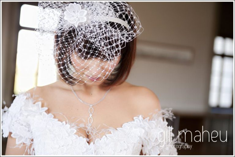 portrait of bride with veil looking down  by Gill Maheu Photography, photographe de mariage
