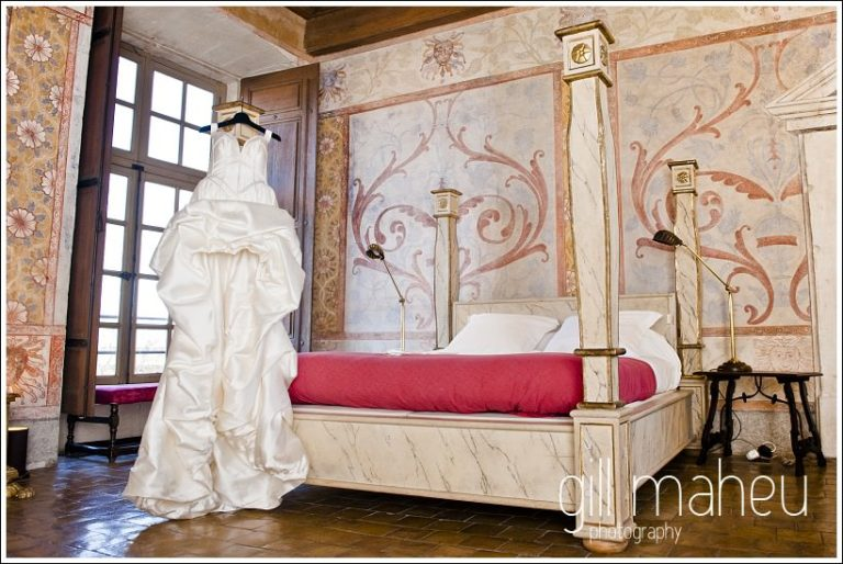 stunning Max Chaoul wedding dress hanging from four poster bed at Chateau de Bagnols by Gill Maheu Photography, photographe de mariage