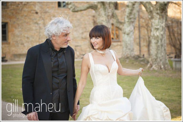 bride and groom walking through courtyard at Chateau de Bagnols wedding by Gill Maheu Photography, photographe de mariage