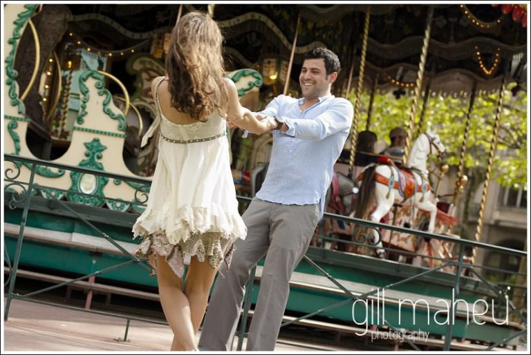 portraits of engagement couple dancing in front of merry go round in Annecy by Gill Maheu Photography, photographe de mariage
