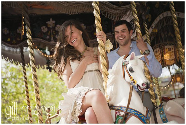 portraits of engagement couple looking at camera from merry go round in Annecy by Gill Maheu Photography, photographe de mariage