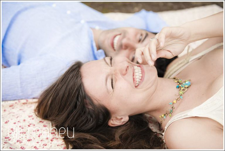 engagement couple lying on picnic blanket laughing, Lake Annecy by Gill Maheu Photography, photographe de mariage