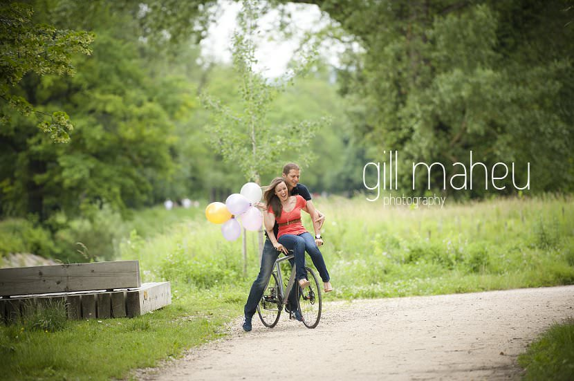 wide angle bride to be sitting on handlebars of bike kissing groom engagement session Geneva by Gill Maheu Photography, photographe de mariage