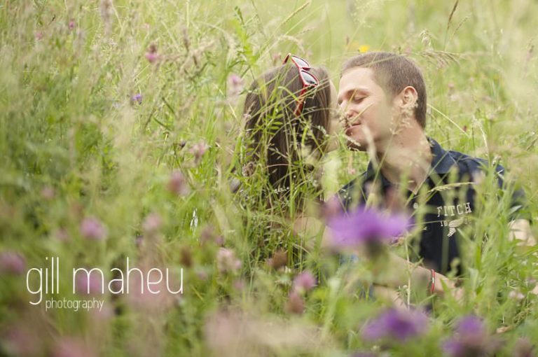 engaged couple kissing in wild flower meadow near Geneva by Gill Maheu Photography, photographe de mariage