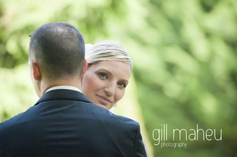 bride looking over grooms shoulder at camera at Hotel Saint Pères wedding by Gill Maheu Photography, photographe de mariage