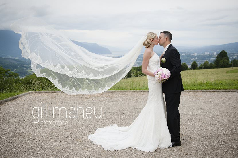 fabulous shot of cathedral veil floating whilst wedding couple kissing in front of view of Lac lake Bourget at Hotel Saint Pères wedding by Gill Maheu Photography, photographe de mariage