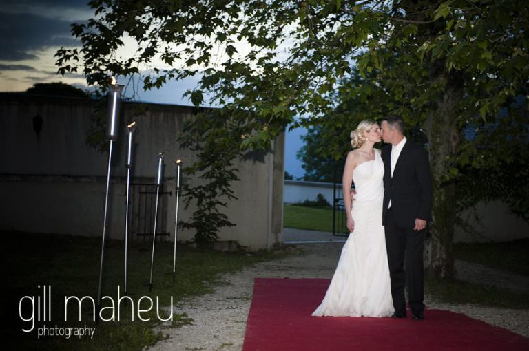 bride and groom kissing on red carpet on way into evening celebrations at Hotel Saint Pères by Gill Maheu Photography, photographe de mariage