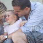 family lifestyle of portrait of young child being cuddled by her parents in a park in Geneva Geneve by Gill Maheu Photography, photographe de famille