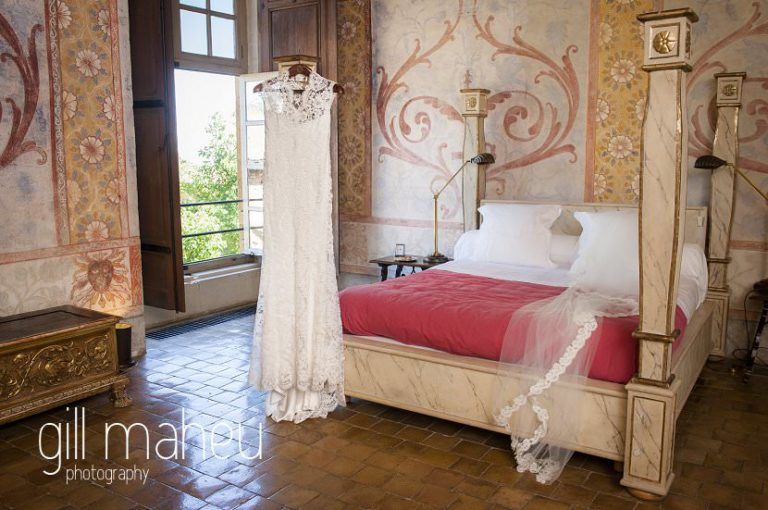Wedding detail of stunning Monique Lhuillier wedding dress hanging on four poster bed at Chateau de Bagnols wedding by Gill Maheu Photography, photographe de mariage