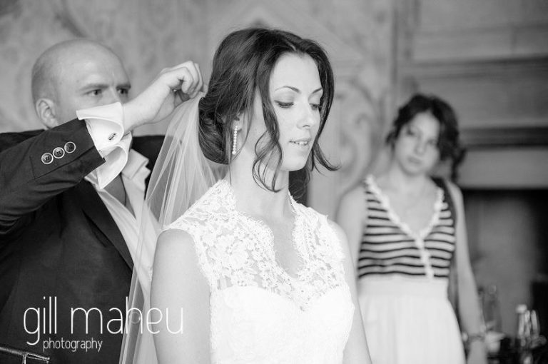 black and white photo of mother pinning on beautiful bride's wedding veil at Chateau de Bagnols wedding by Gill Maheu Photography, photographe de mariage