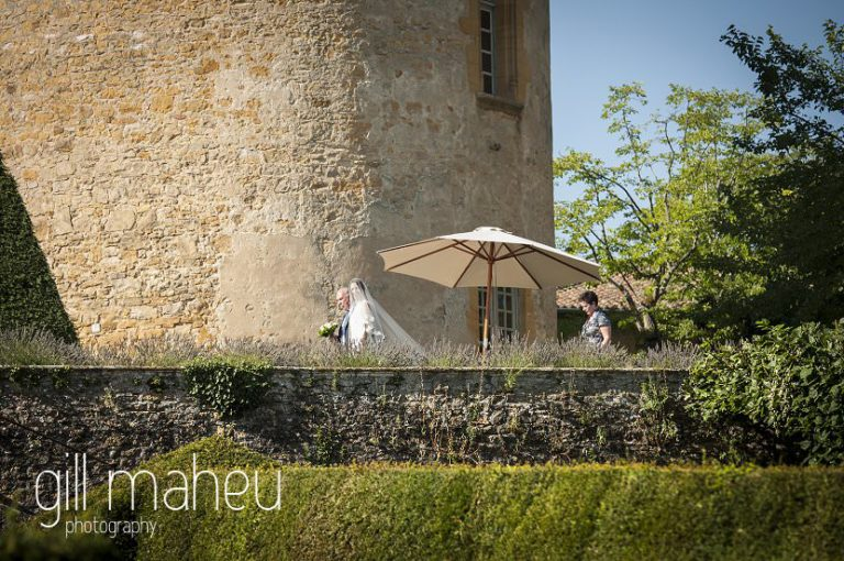 Bride and father walking through garden of castle towards wedding ceremony at Chateau de Bagnols wedding by Gill Maheu Photography, photographe de mariage