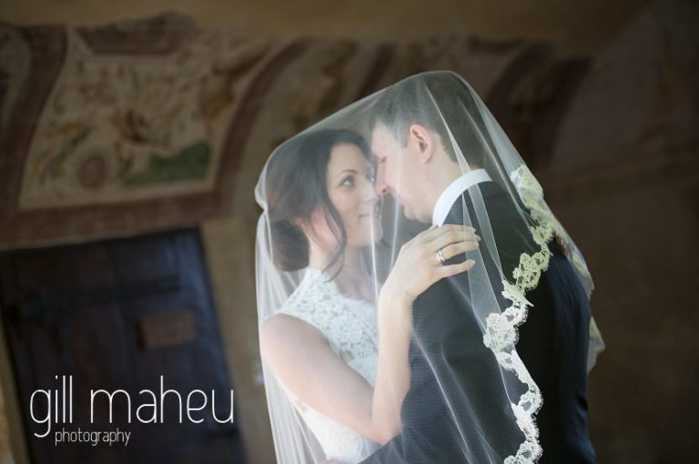 intimate romantic photo of bride and groom kissing under veil at Chateau de Bagnols wedding by Gill Maheu Photography, photographe de mariage