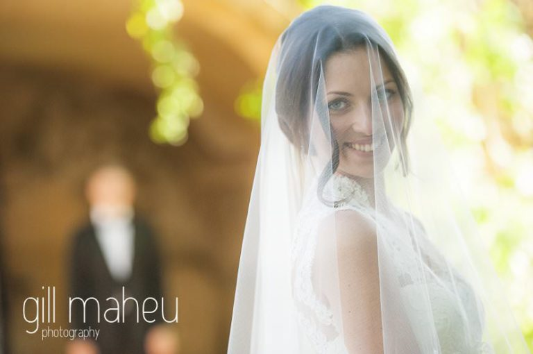 portrait of bride with veil with groom in background outer courtyard Chateau de Bagnols wedding by Gill Maheu Photography, photographe de mariage