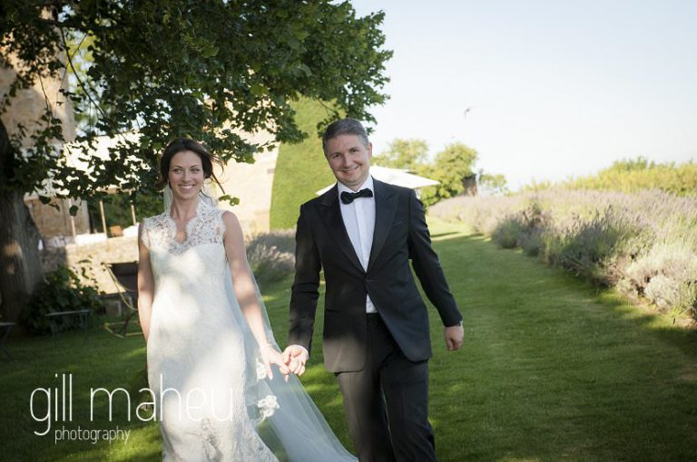 bride and groom walking through gardens at Chateau de Bagnols wedding by Gill Maheu Photography, photographe de mariage