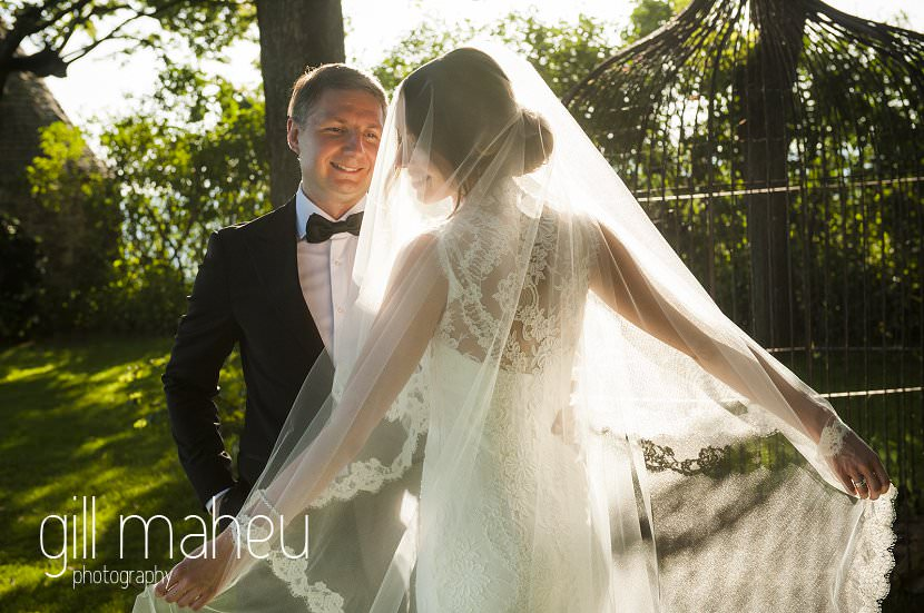 bride and groom in evening sunlight bride is silhouetted holding veil at Chateau de Bagnols wedding by Gill Maheu Photography, photographe de mariage