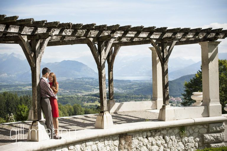 lifestyle portrait of newly wed couple kissing under pergola in front of stunning viwe of Alps at Chateau d'Avenieres near Annecy by Gill Maheu Photography, photographe de mariage et de famille