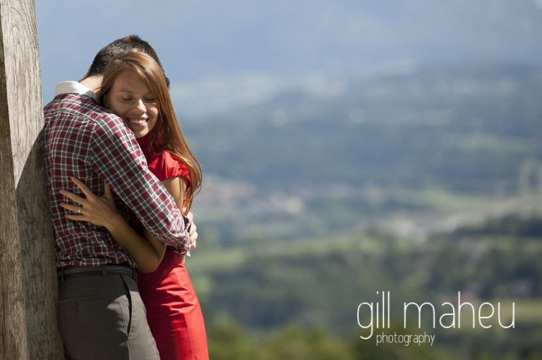 lifestyle portrait of newly wed couple kissing in front of stunning viwe of Alps at Chateau d'Avenieres near Annecy by Gill Maheu Photography, photographe de mariage et de famille