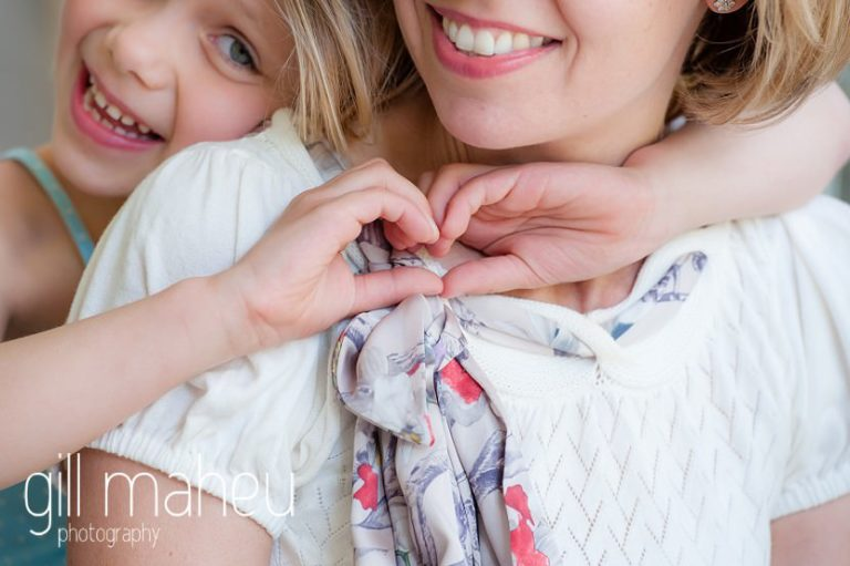 portrait of little girl making heart shape with hands around neck of her Mum at home in Geneva Geneve by Lifestyle photographer Gill Maheu Photography, photographe de famille