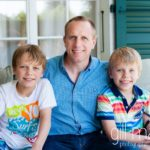 portrait of dad and two sons at home in Geneva Geneve by Lifestyle photographer Gill Maheu Photography, photographe de famille