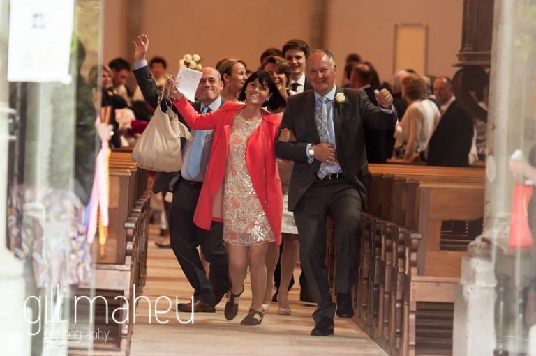parents of the bride and groom dancing out of Lutry church at Chateau de Glerolles wedding by Gill Maheu Photography, photographe de mariage