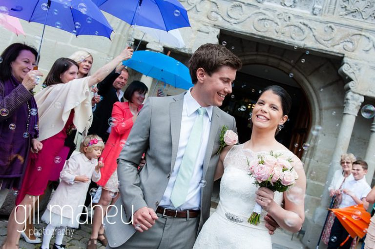 bride and groom coming out of Lutry church at Chateau de Glerolles wedding by Gill Maheu Photography, photographe de mariage
