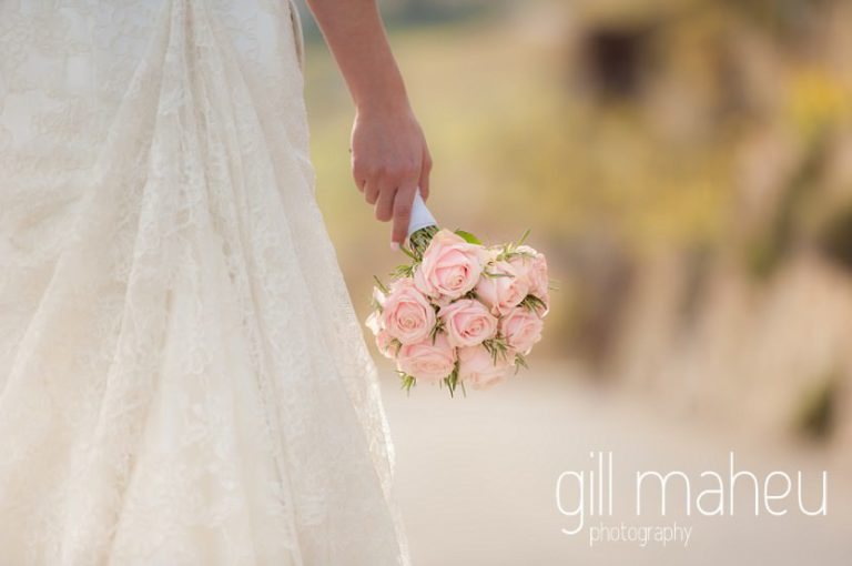 wedding detail of bride holding stunning pink rose wedding bouquet in the vineyards above Chateau de Glerolles wedding by Gill Maheu Photography, photographe de mariage