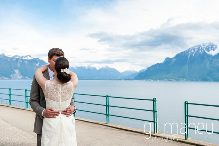full length portrait of bride and groom in front of stunning view of Lac Leman in the vineyards above Chateau de Glerolles wedding by Gill Maheu Photography, photographe de mariage