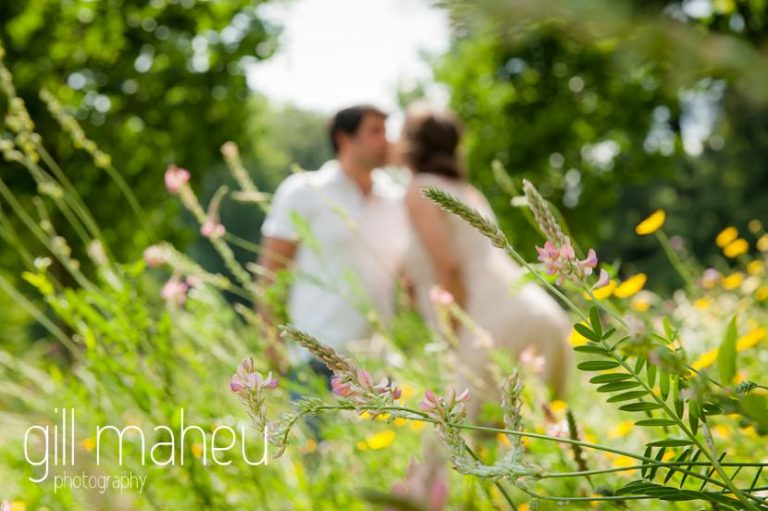 future parents through wildflower meadow in maternity session in Parc de la Tete D'or in Lyon, by Gill Maheu Photography, photographe de Grossesse et lifestyle