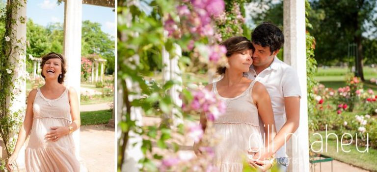 beautiful pink roses with future  parents embarcing in the background at future Papa gently caressing baby bump in the woodland at maternity session in Parc de la Tete D'or in Lyon, by Gill Maheu Photography, photographe de Grossesse et lifestyle