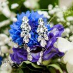 close up of diamond earrings on cornflower wedding bouquet at Abbaye de Talloires, Annecy wedding by Gill Maheu Photography, photographe de mariage