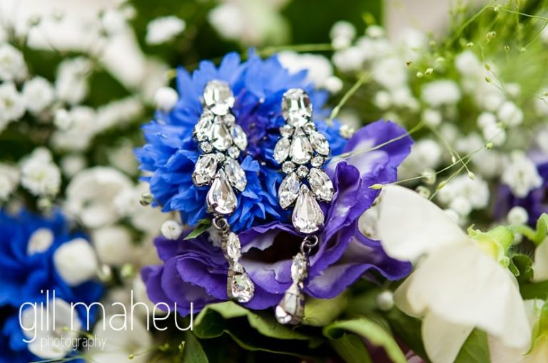 close up of diamond earrings on cornflower wedding bouquet at Abbaye de Talloires, Annecy wedding by Gill Maheu Photography, photographe de mariage