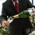 a glass of chjampagne being poured at the vin d'honneur cocktail at Abbaye de Talloires, Annecy wedding by Gill Maheu Photography, photographe de mariage