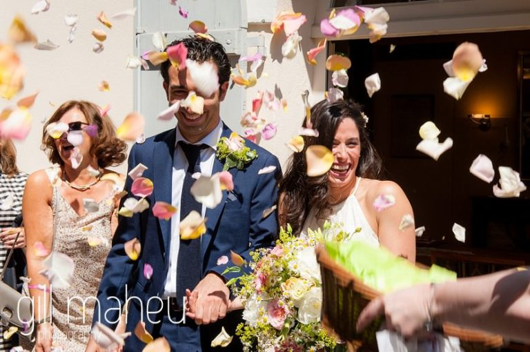 bride and groom coming out under rose petal confetti after civil wedding ceremony at the Mairie de Versoix, Geneva  by Gill Maheu Photography, photographe de mariage