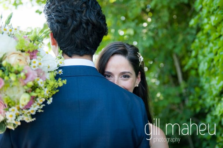 portrait of bride peeking over groom's shoulder in the gardens of the Mairie de Versoix, Geneva after their civil wedding ceremony by Gill Maheu Photography, photographe de mariage