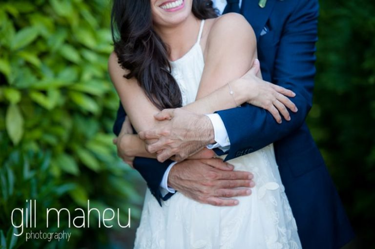 close up of bride and groom's arms wrapped around each other in the gardens of the Mairie de Versoix, Geneva after their civil wedding ceremony by Gill Maheu Photography, photographe de mariage