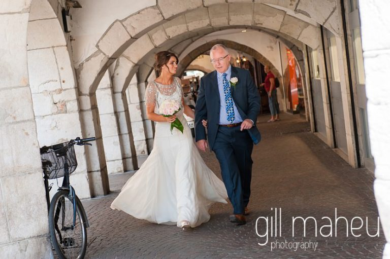 bride and her father walking through the arcades of Annecy old town towards Notre Dame de Liesse and Hotel Imperial Palace, Annecy wedding by Gill Maheu Photography, photographe de mariage