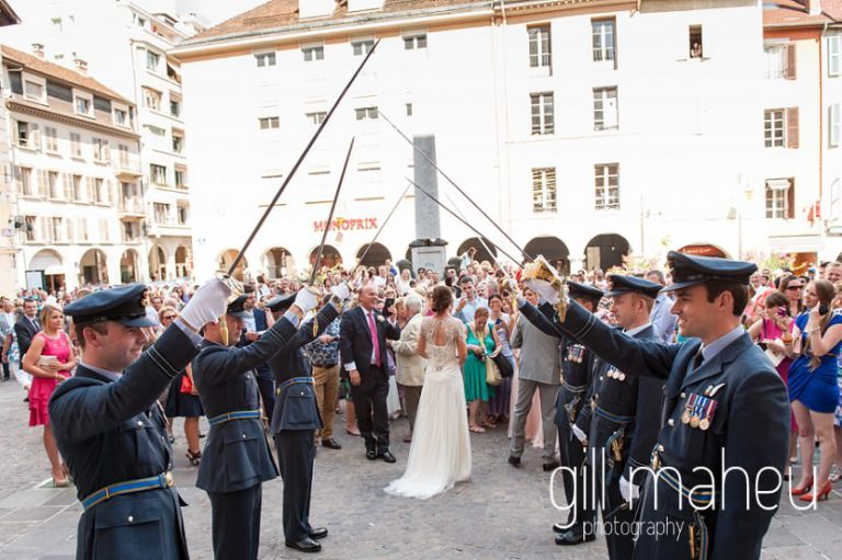 bride and groom kissing under drawn sword military guard of honour on the steps of Notre Dame de Liesse, Annecy wedding by Gill Maheu Photography, photographe de mariage