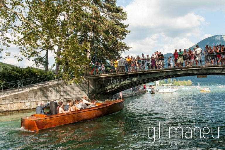 bride and groom and bridal party in a gorgeous mahogany Riva boat making their way from le Pont des Amours towards their Hotel Imperial Palace, Annecy wedding by Gill Maheu Photography, photographe de mariage