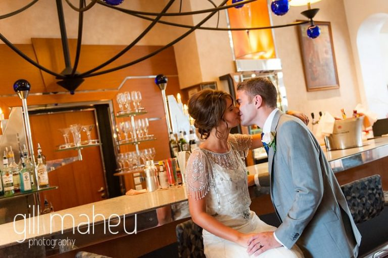 bride and groom kissing in the art deco bar of the Hotel Imperial Palace, Annecy wedding by Gill Maheu Photography, photographe de mariage