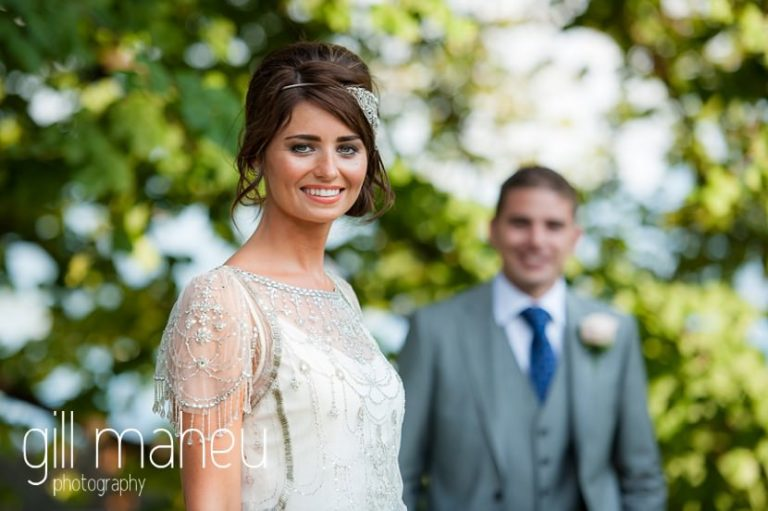 portrait of bride with groom in distance in the gardens of the Hotel Imperial Palace, Annecy wedding by Gill Maheu Photography, photographe de mariage