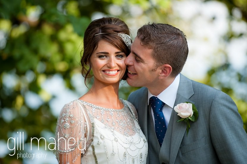 Groom kissing smiling bride in the gardens of the Hotel Imperial Palace, Annecy wedding by Gill Maheu Photography, photographe de mariage