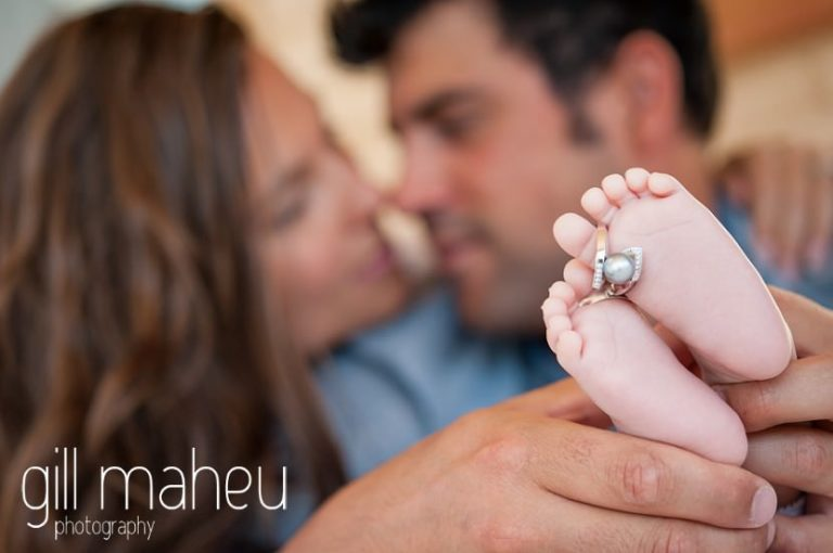 close up of adorable little feet with parents wedding rings during new baby new family portrait session in Annecy by Gill Maheu Photography, photographe de bébé et famille