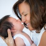 tiny baby in arms of mum being kissed on the nose during new baby new family portrait session in Annecy by Gill Maheu Photography, photographe de bébé et famille