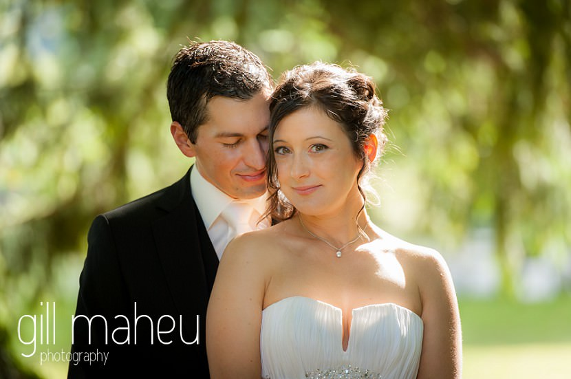 portrait of Groom kissing bride in sunlit gardens at Nantua, Jura wedding by Gill Maheu Photography, photographe de mariage